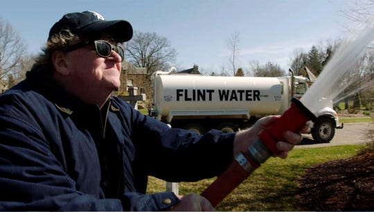 """Michael Moore sprays """"Flint water"""" at the Michigan State Capitol building in Lansing in his documentary """"Fahrenheit 11/9."""""""