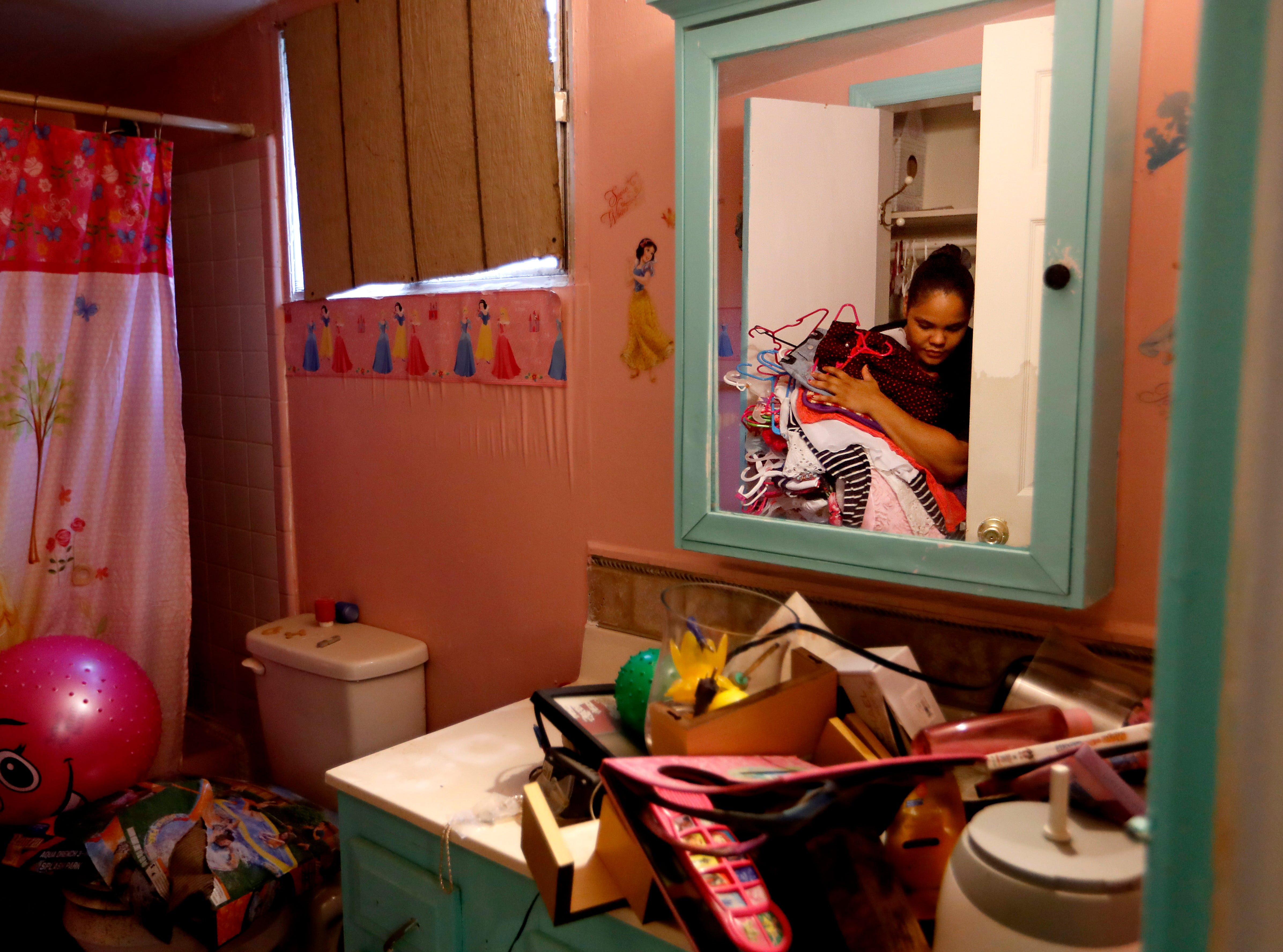"Rosemary Acevedo-Gonzalez retrieves clothing from her daughter's bathroom as she returns to their home for the first time since it was flooded in the aftermath of Hurricane Florence in Spring Lake, N.C., Wednesday, Sept. 19, 2018. ""This is the only thing I can get,"" said Acevedo-Gonzalez of what was salvageable. ""That's it. I'm done."""