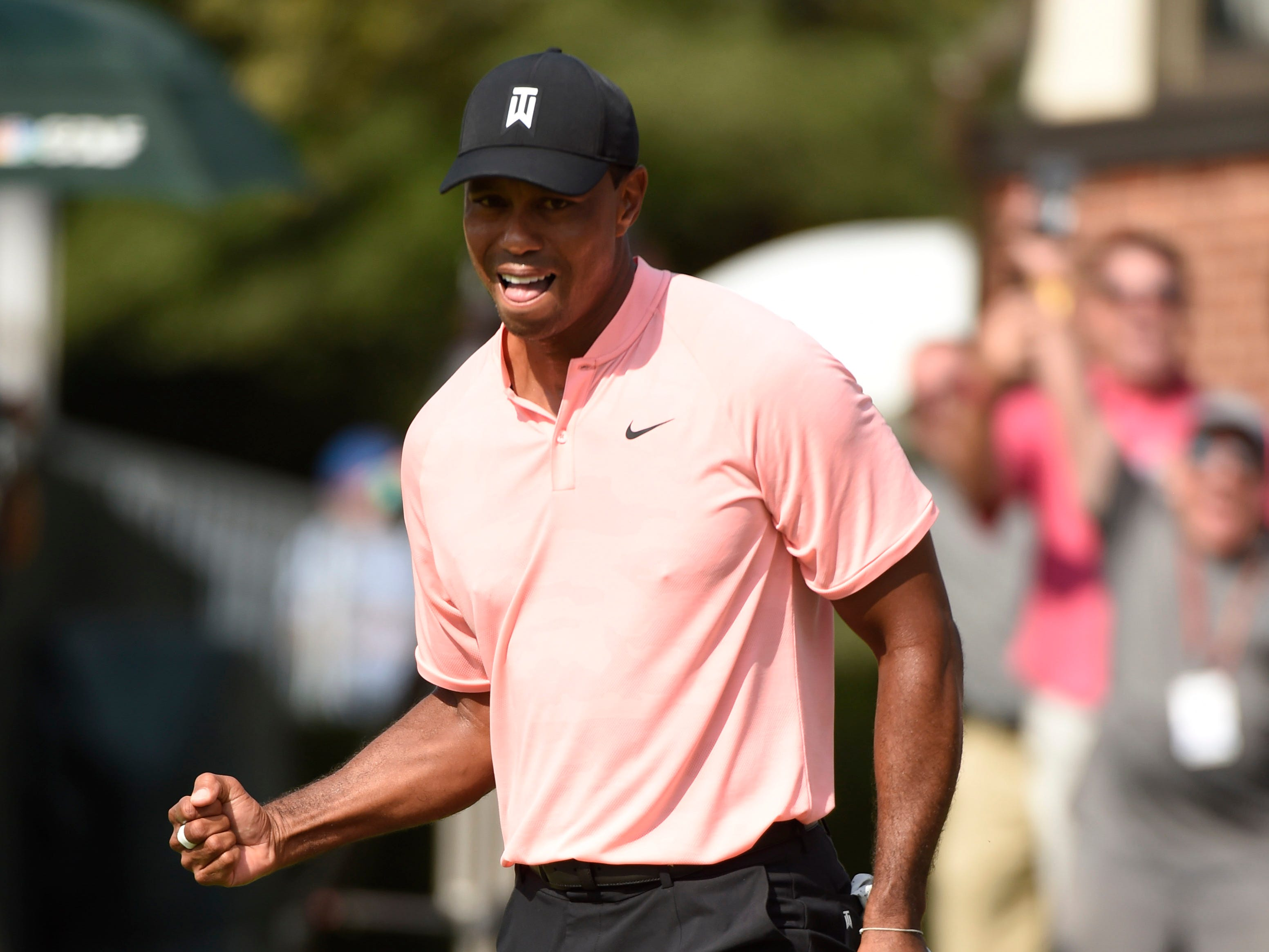 Tiger Woods celebrates making a putt for eagle on the 18th hole during the first round of the Tour Championship at East Lake Golf Club.