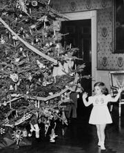 The Blue Room is traditionally the spot for the White House Christmas tree. In this 1961 photo, Caroline Kennedy gets a look at the tree before a party for White House employees. First lady Jacqueline Kennedy began the reacquisition of the Bellange furniture that has been restored and will be reinstalled in the Blue Room this fall.