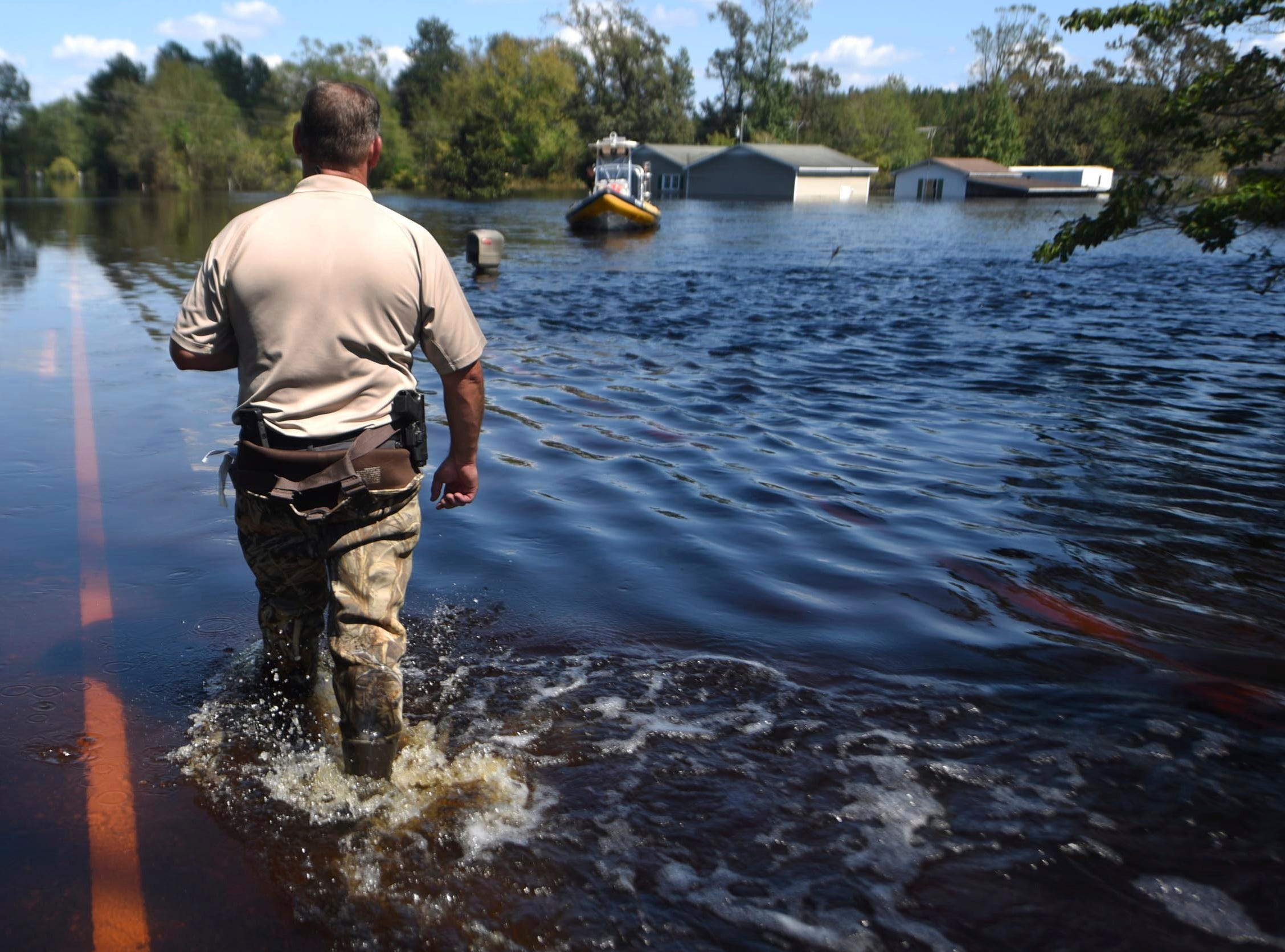 Lt. Keith Ramsey with the Pender County Sheriff's Office walks out to a boat while taking part in rescue operations in Burgaw, N.C., Wednesday, Sept. 19, 2018. A large area east of Burgaw is experiencing severe flooding from the Northeast Cape Fear River due to the rains from Hurricane Florence.