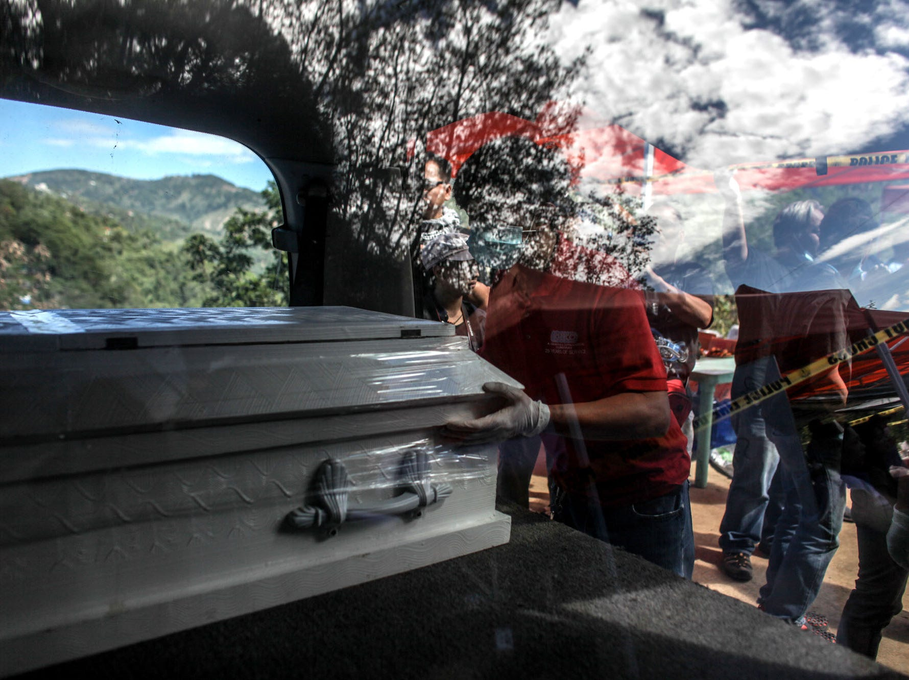 Workers place inside a vehicle a coffin of a victim killed by a landslide on Sept. 19, 2018 in Itogon, Benguet province, Philippines.