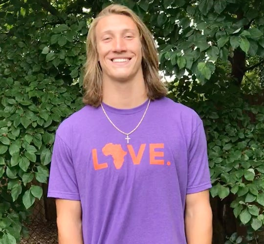 Clemson quarterback Trevor Lawrence wears one of Orphan Aid, Liberia's signature LOVE. t-shirts.