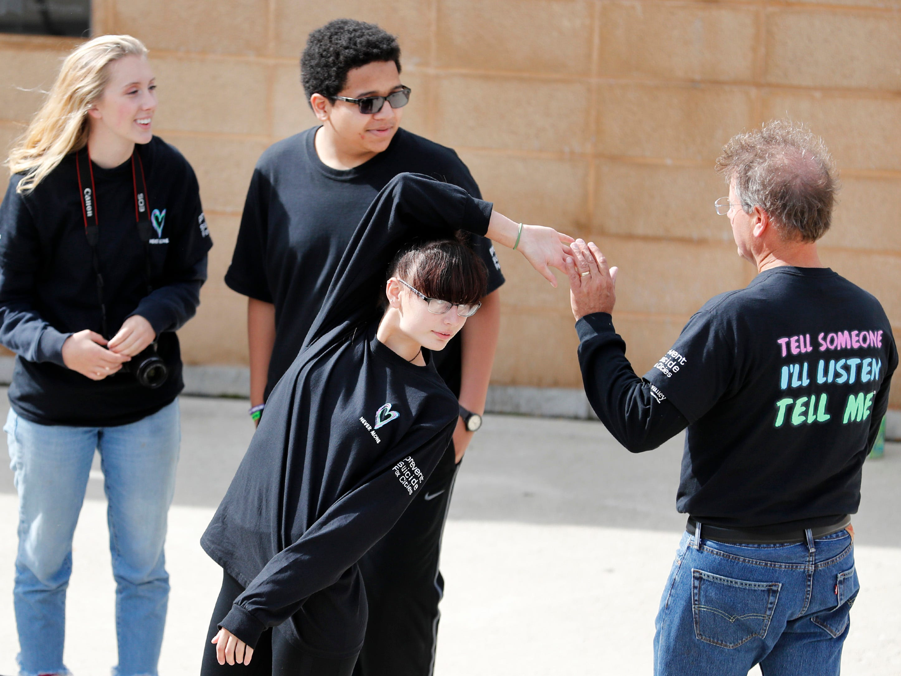Student organizers of Little Chute High School's mental health wellness fair Amidala Czaja and Keaton Duffeck stand with the third organizer, Montannah Weiss, as she high fives Little Chute school counselor Kevin Pratt Friday, Sept. 21, 2018, in Little Chute, Wis.