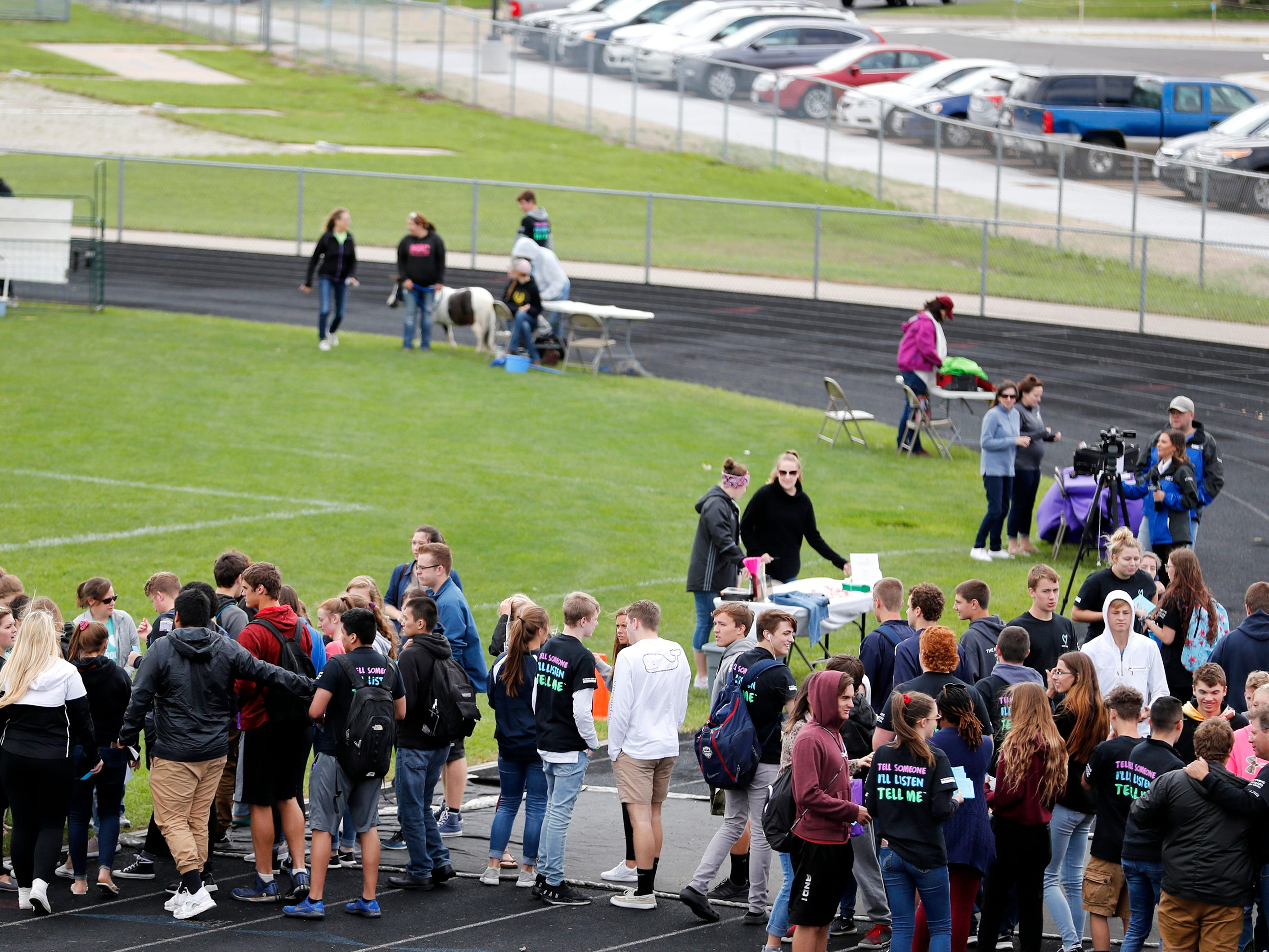 Little Chute High School seniors start to make their way around the track to look at booths during Little Chute's mental health wellness fair Friday, Sept. 21, 2018, in Little Chute, Wis.