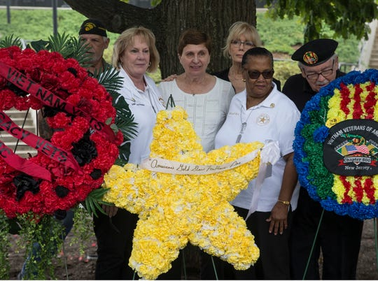 Gold Star Mothers Shirley Parrello of West Milford, Helen Gurbisz of Eatontown, and Eula Morris of Freehold stand behind the American Gold Mother's wreath during the ceremony. The POW/MIA Gold Star Mothers Recognition Ceremony takes place at the New Jersey Vietnam Veterans' Memorial. The ceremony honors women as well as others who lost family members during military conflict. 