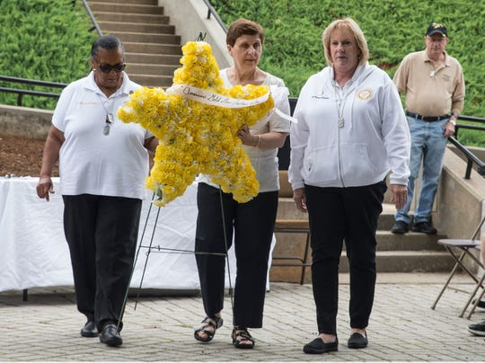 Gold Star Mothers Eula Morris of Freehold, Helen Gurbisz of Eatontown, and Shirley Parrello of West Milford present the American Gold Mother's wreath during the ceremony. The POW/MIA Gold Star Mothers Recognition Ceremony takes place at the New Jersey Vietnam Veterans' Memorial. The ceremony honors women as well as others who lost family members during military conflict. 