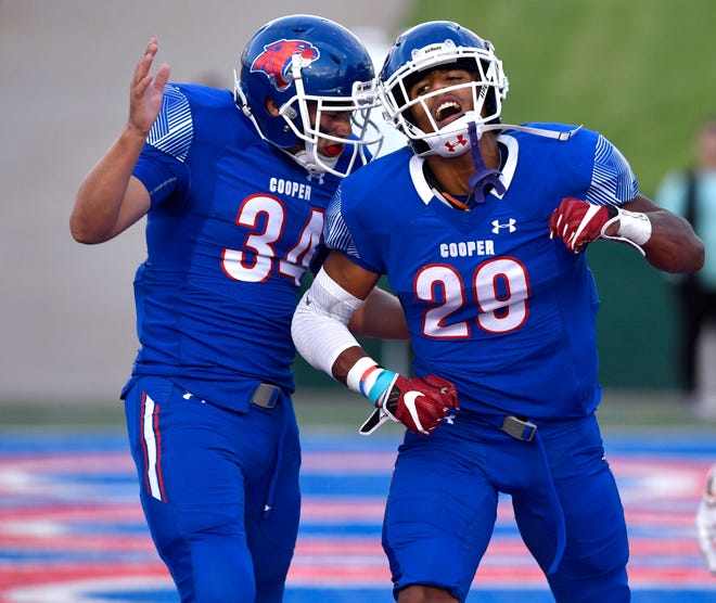Cooper running back Xavier Wishert (left) congratulates teammate Aeneas Favors on his touchdown run. Cooper and Wylie faced each other for the first time last Thursday at Shotwell Stadium. Cooper won 48-0. It was just the third varsity game for Wishert, a freshman fullback who began the season playing freshman ball.