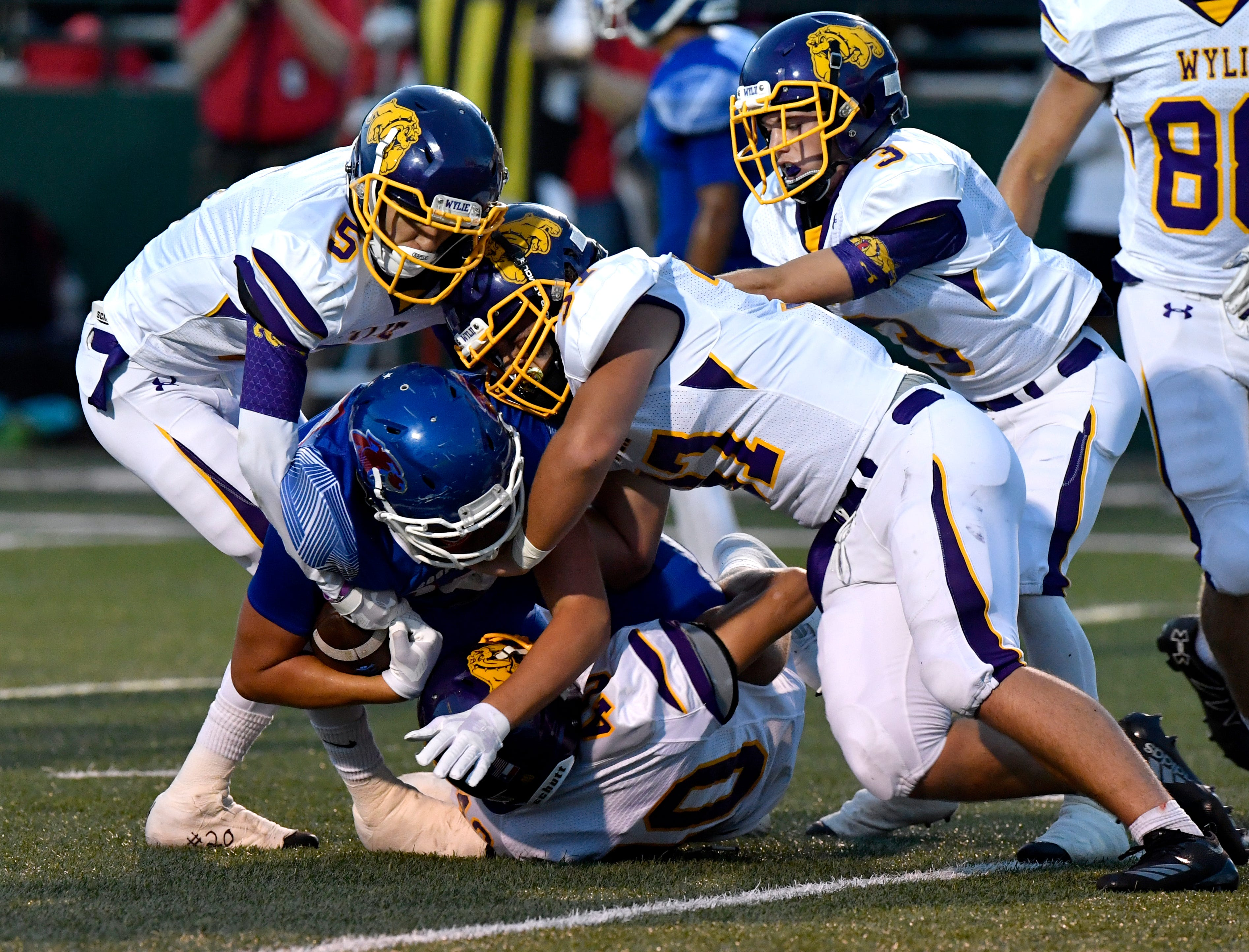 Wylie defenders Calvin Tiner (5), Cason Hanna (37) and Jaden Speegle (3) bring down Cooper's Braiden Hill during the first-ever game between the two teams. The Bulldogs are trying to bounce back from that 48-0 defeat and 0-4 start this week at Brownwood.