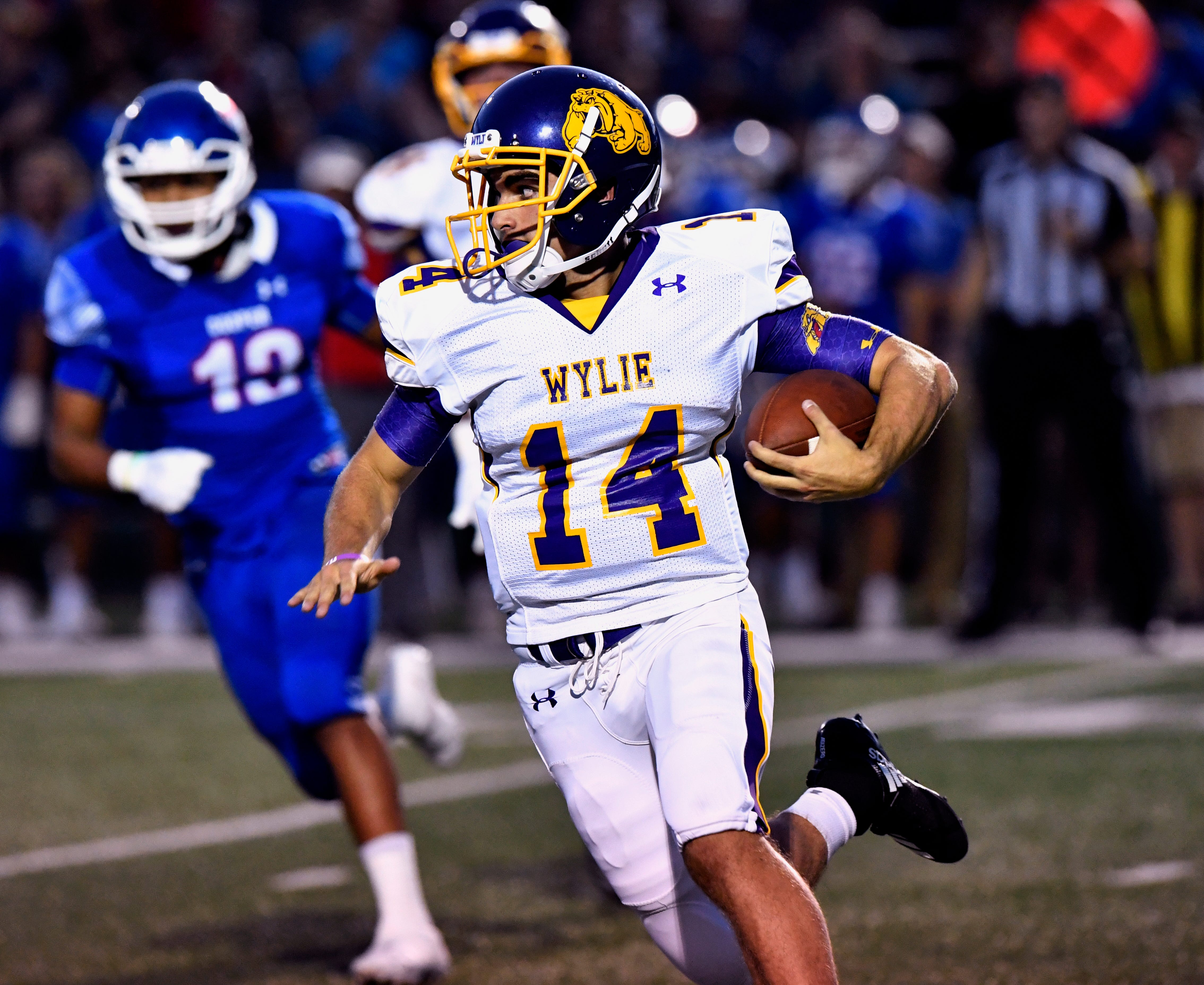 Wylie quarterback Jaxon Hansen scrambles with the ball in Thursday's 48-0 loss to the Cooper Cougars at Shotwell Stadium.
