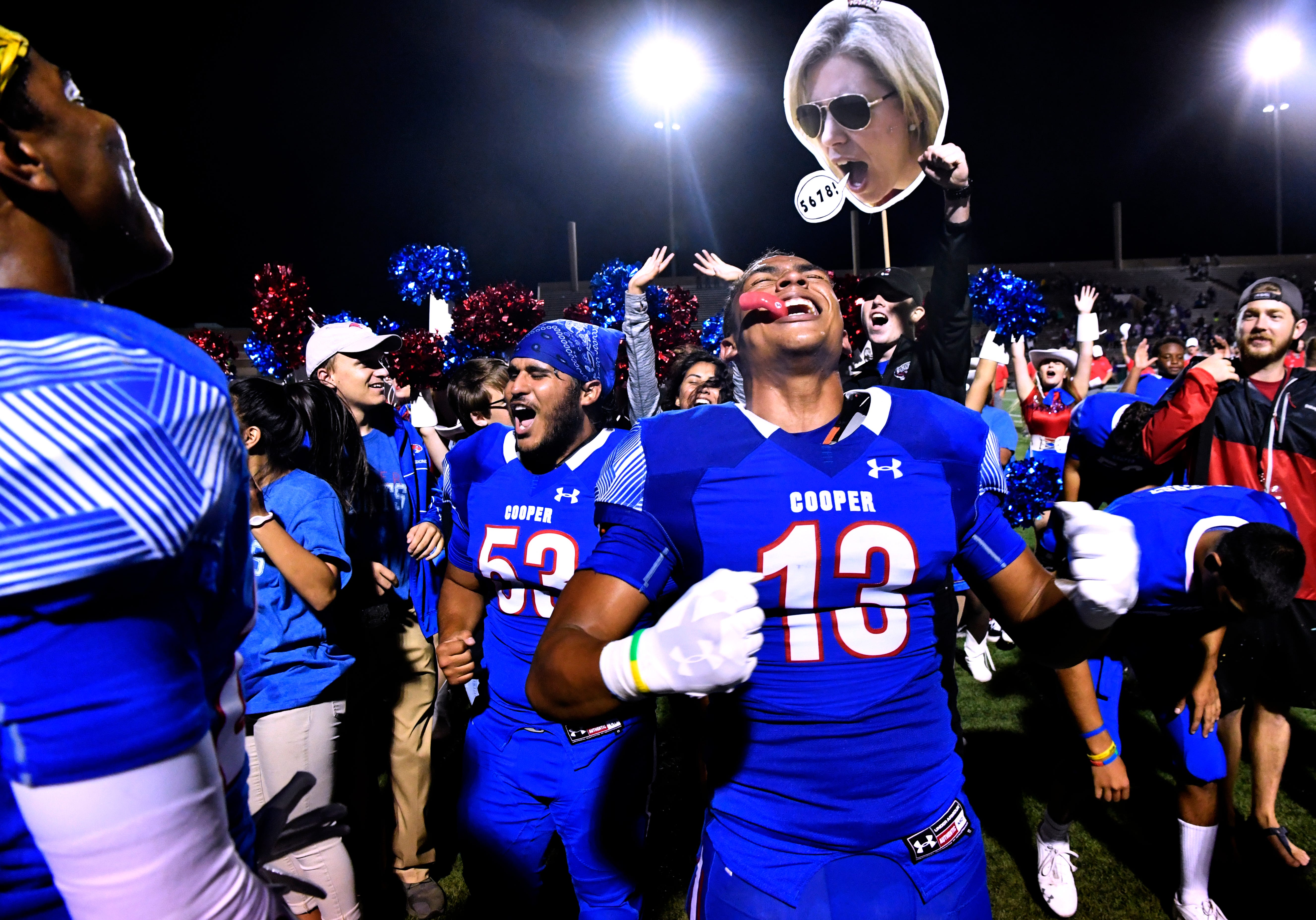 With a cutout head floating in the background,Tavian Bonds (center) celebrates Cooper High School's 48-0 win over Wylie High School Thursday Sept. 20, 2018.