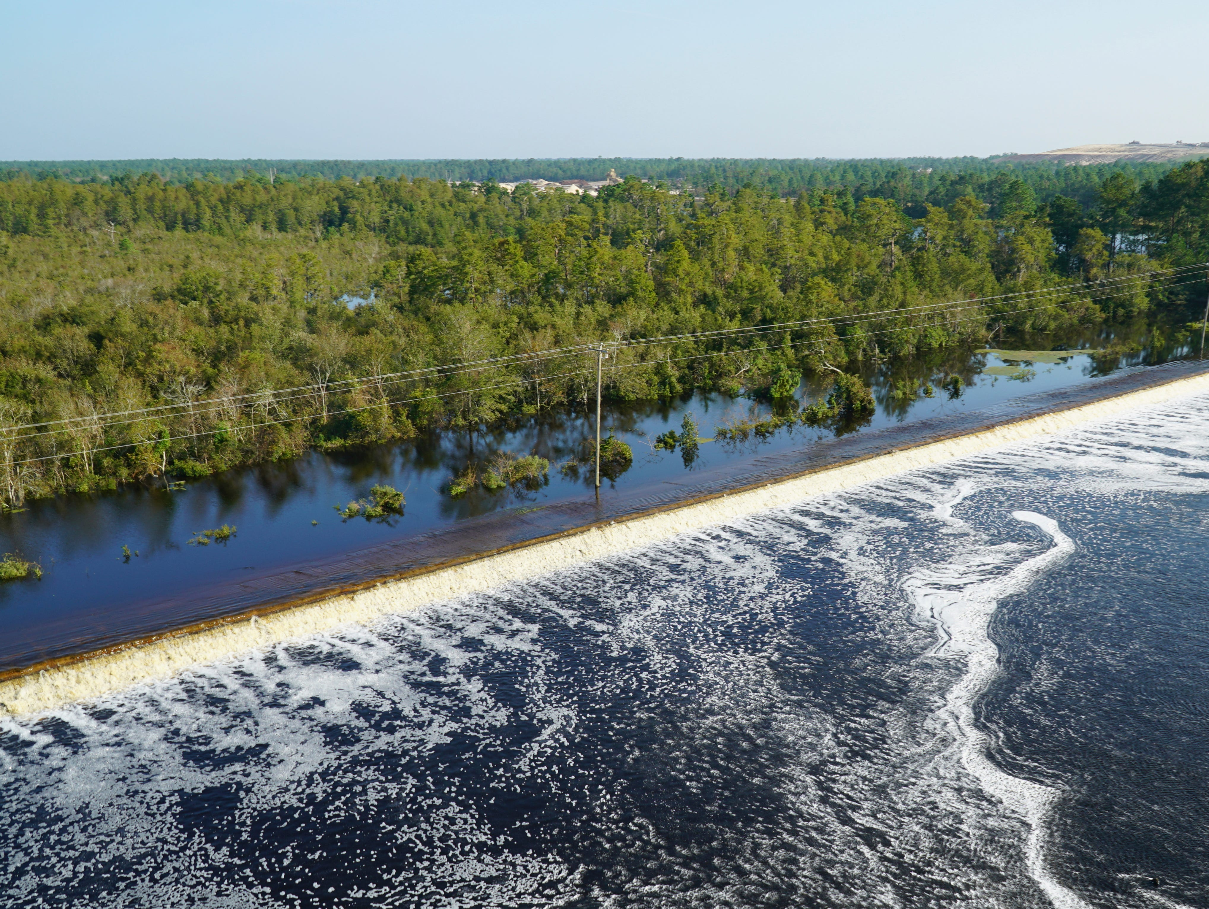 In this drone photo released by Duke Energy, flooding from the swollen Cape Fear River overtops an earthen dike at Sutton Lake, a 1,100-acre lake at the L.V. Sutton Power Station near Wilmington, N.C. , on Sept. 20, 2018. Duke Energy activated a high-level emergency alert at the retired coal-fired power plant due to the flooding, raising concerns of a potential breach.