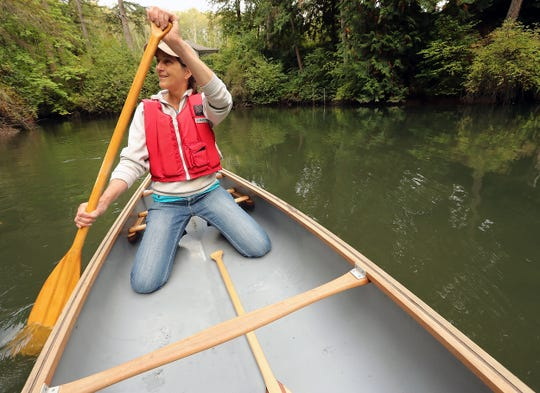 Jane Stone, executive director of the Bainbridge Island Land Trust, paddles a canoe into the estuary of the Miller-Kirkman Preserve.