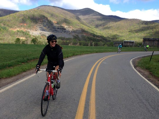 """A cyclist on a tour with Velo Girl Rides passes an area in the North Fork Valley in which scenes from the award-winning film """"Three Billboards Outside Ebbing, Missouri"""" were shot."""