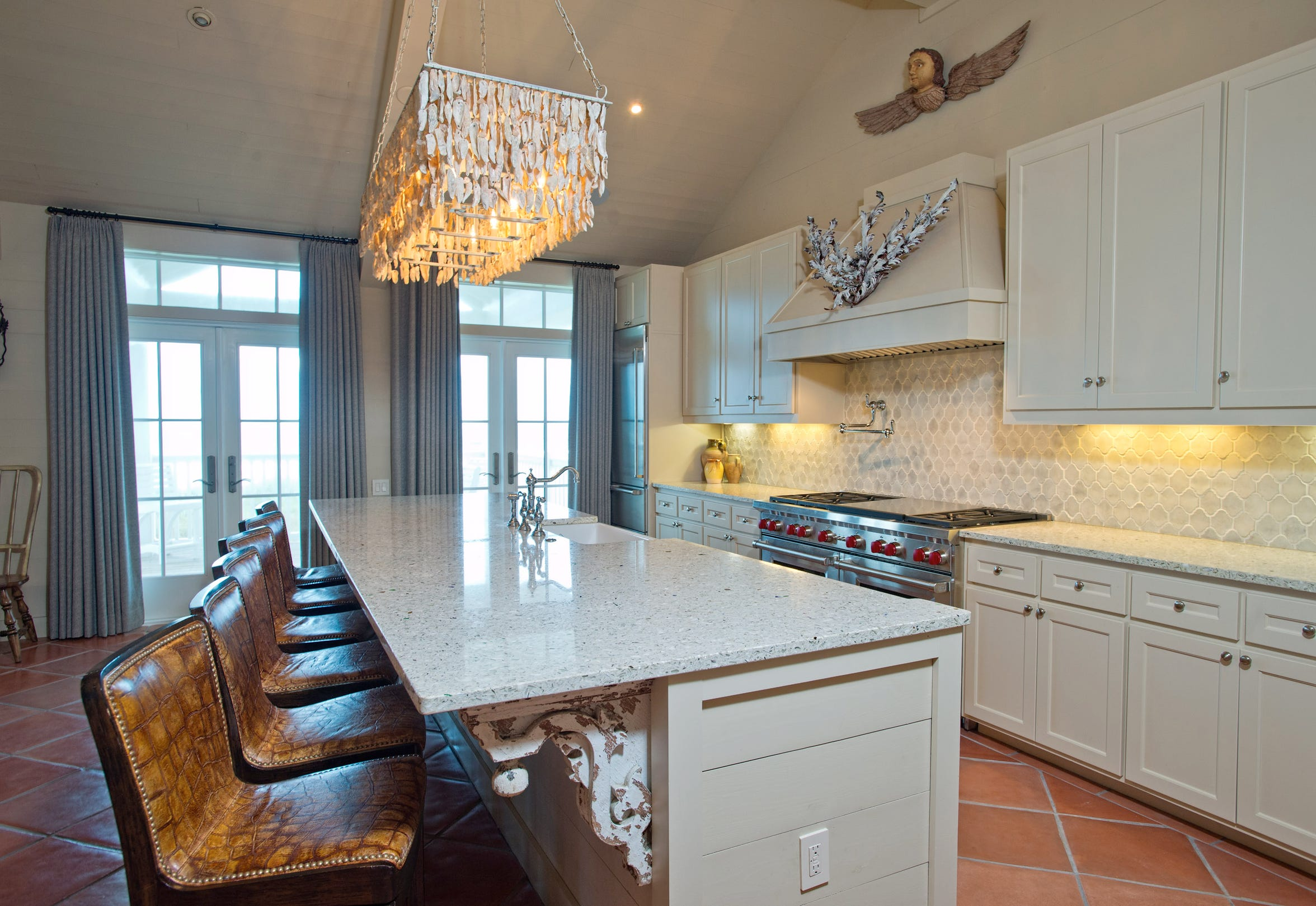 The open kitchen has an island bar with seating for six, two refrigerators and a commercial style Wolf gas range.