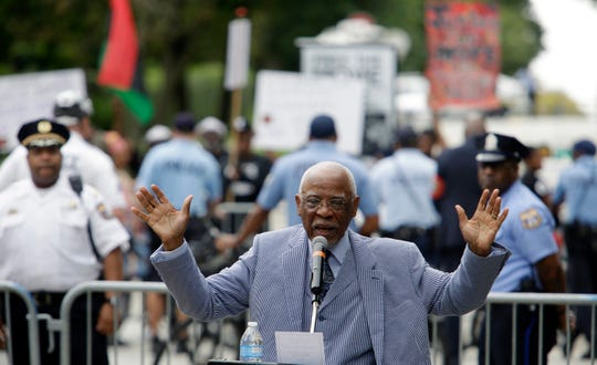 Former Philadelphia Mayor W. Wilson Goode Sr. speaks to supporters, as protesters demonstrate in the background, during a ceremony to celebrate the naming of a street after him Friday Sept. 21, 2018 in Philadelphia. Goode said he was responsible for dropping a bomb on a home full of people 33 years ago, but said he would not be defined by one day of his life_ the 1985 police bombing of the MOVE headquarters that killed 11 people and destroyed more than 60 rowhomes. (AP Photo/Jacqueline Larma)