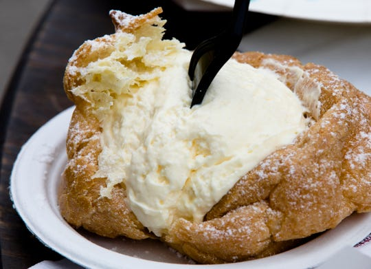 Giant Cream Puff from Schmidt's of German Villageduring Oktoberfest Zinzinnati on Friday, Sept. 21, 2018, in downtown Cincinnati.