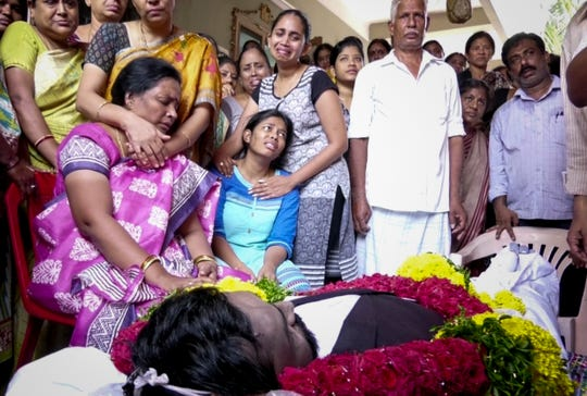 Prudhvi Raj Kandepi's mother and sister are comforted by family, friends and neighbors as they begin the Hindu funeral rituals outside their home in Tenali in the state of Andhra Pradesh in India on Wednesday, September 12, 2018.