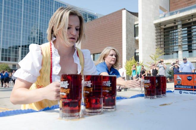 Randi Rico picks up beer during the Gemuetlichkeit Games to kick off Oktoberfest Zinzinnati weekend, Friday, Sept. 21, 2018, in downtown Cincinnati.