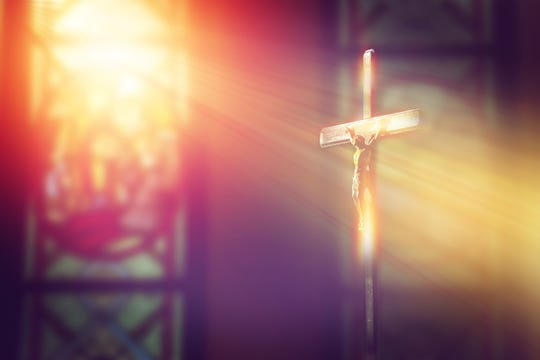 Jesus on the cross in church with ray of light from stained glass