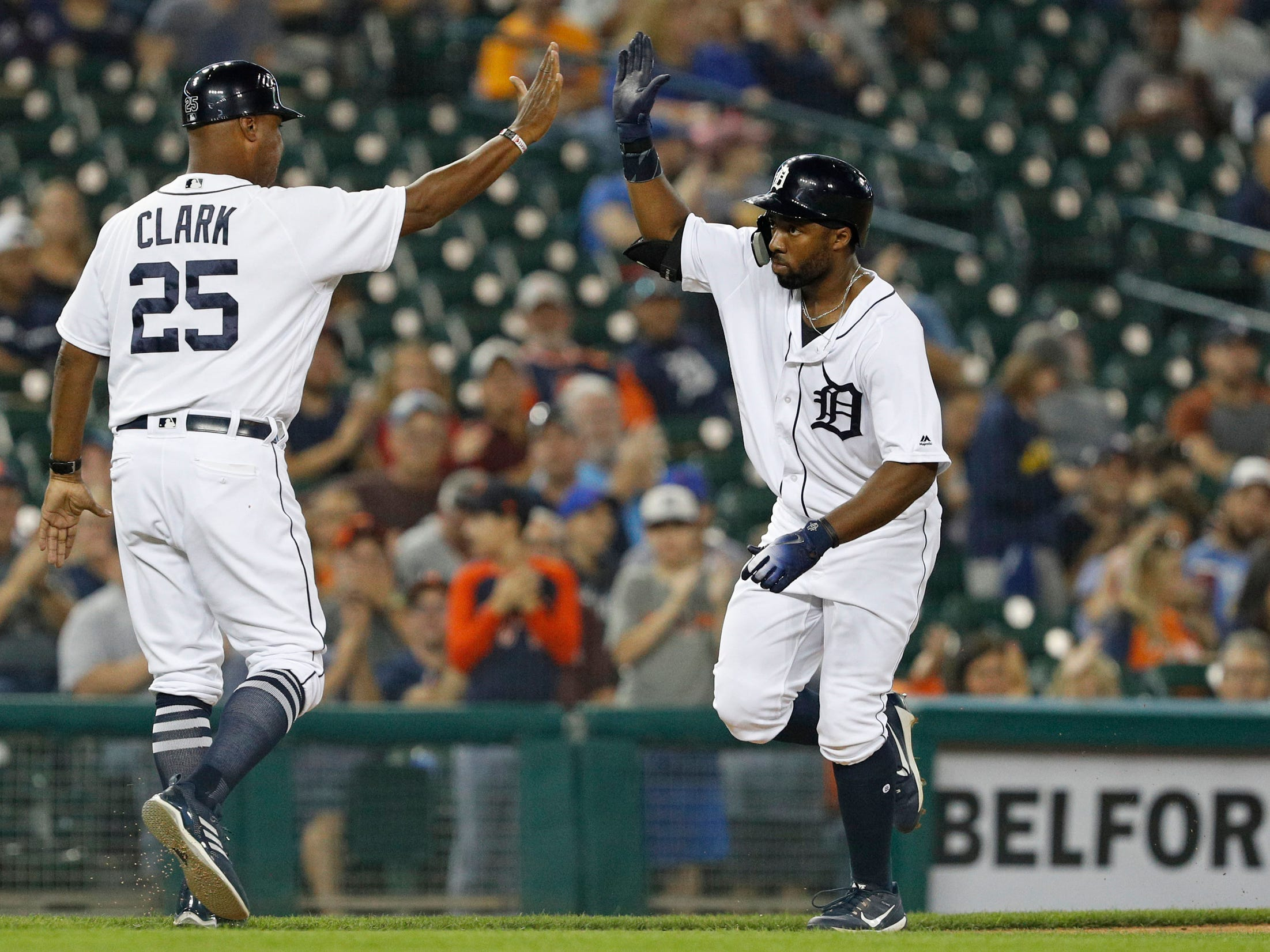 Detroit Tigers left fielder Christin Stewart high-fives third base coach Dave Clark after hitting a three-run home run in the second inning against the Kansas City Royals at Comerica Park on Thursday, Sept. 20, 2018, in Detroit.