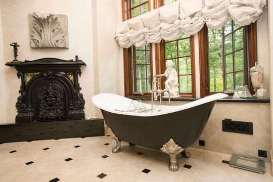 The bath in the owners' suite has a Parisian flair with an antique cast-iron fireplace and a carved-foot tub.