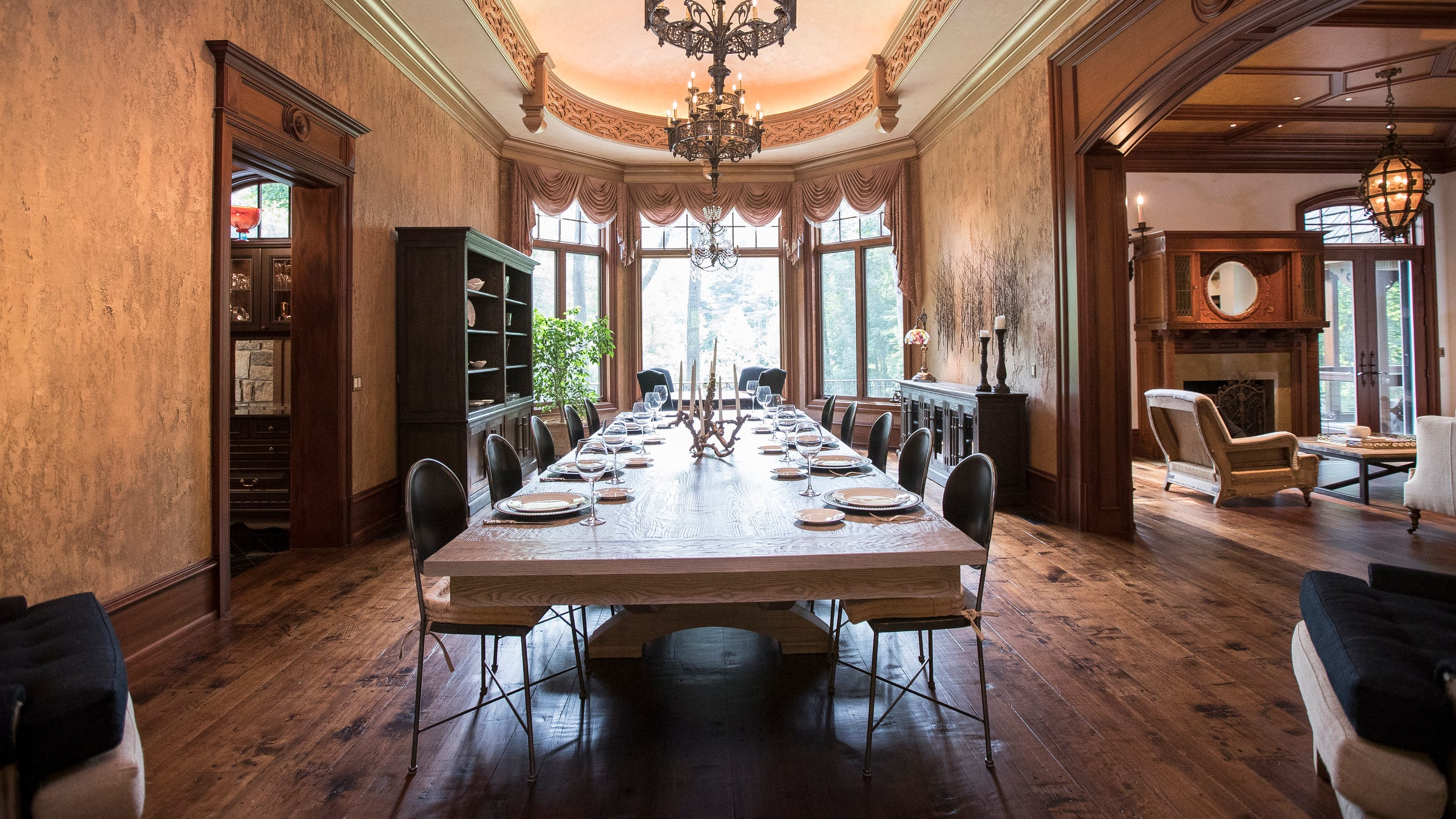 The opulent formal dining room has deep plaster carving around the ceiling and Venetian plaster finish on the walls.  The wide-plank wood floors were hand distressed by an artisan, rather than bought pre-distressed. The living room is at right.