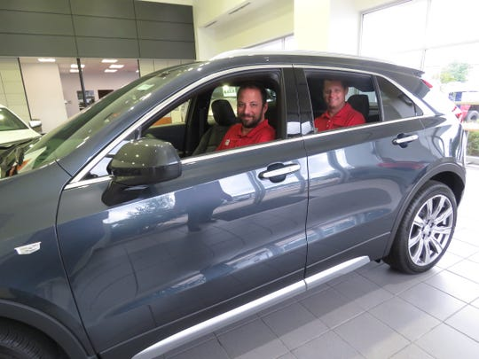 Thompson Buick GMC Cadillac in Missouri has three XT4's in stock. Troy Thompson, used car sales manager, and Drew Givens, new car sales manager, sit in one.