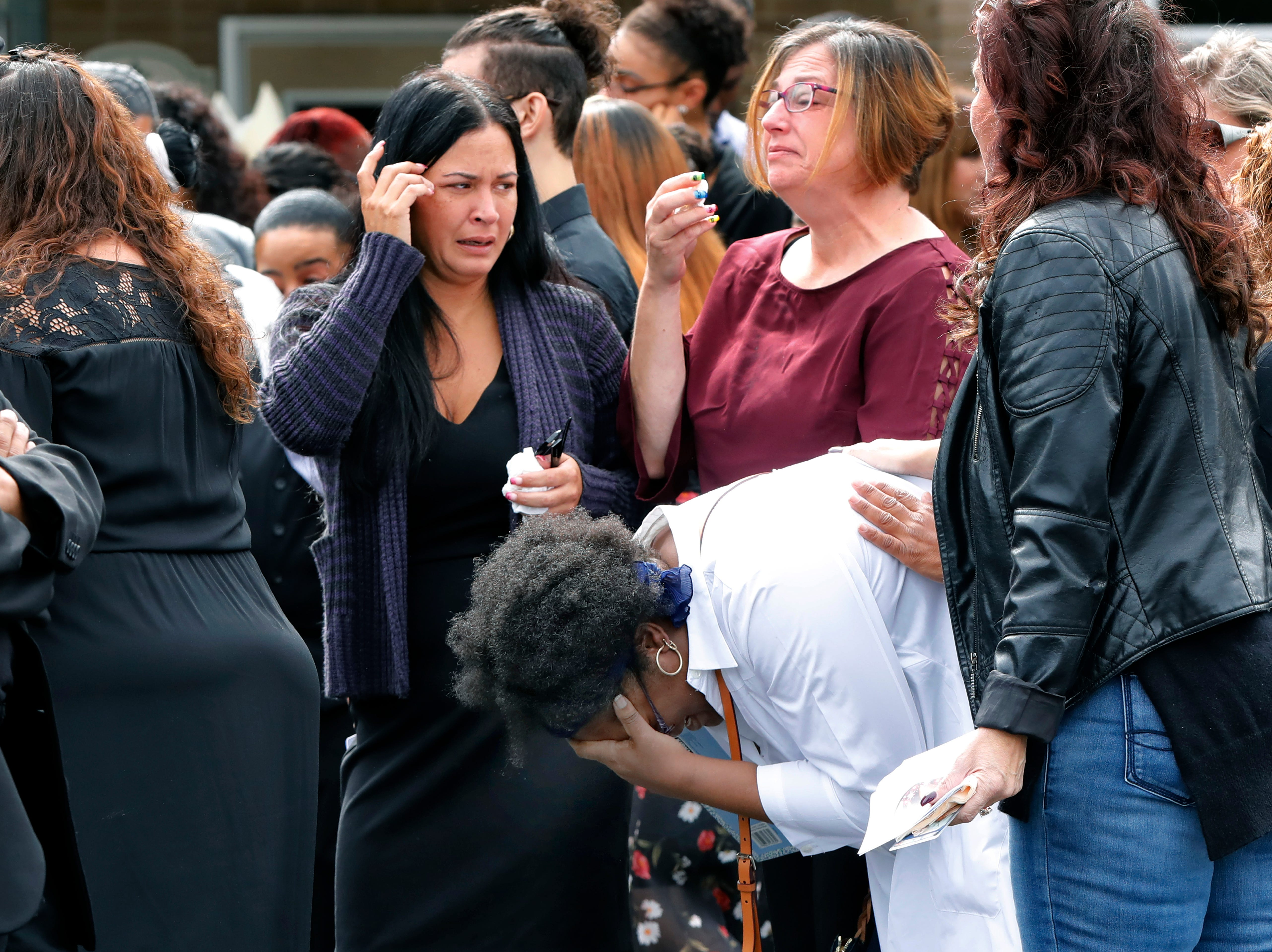Mourners gather outside Saint Anne's Roman Catholic Church following the funeral for Evelyn Rodriguez, in Brentwood, N.Y., Friday, Sept. 21, 2018. Rodriguez, 50, is a mother recognized by President Donald Trump for turning grief over her daughter's suspected gang killing into a crusade against the gang MS-13. She was struck and killed by an SUV on Sept. 14 after a heated confrontation with the driver over the placement of a memorial to her slain daughter, Kayla Cuevas.