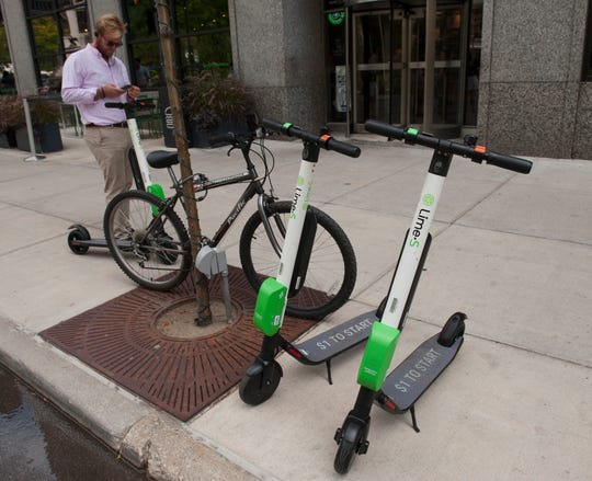 A Lime scooter customer uses his phone app to unlock a scooter in downtown Detroit on Tuesday, August 28, 2018.