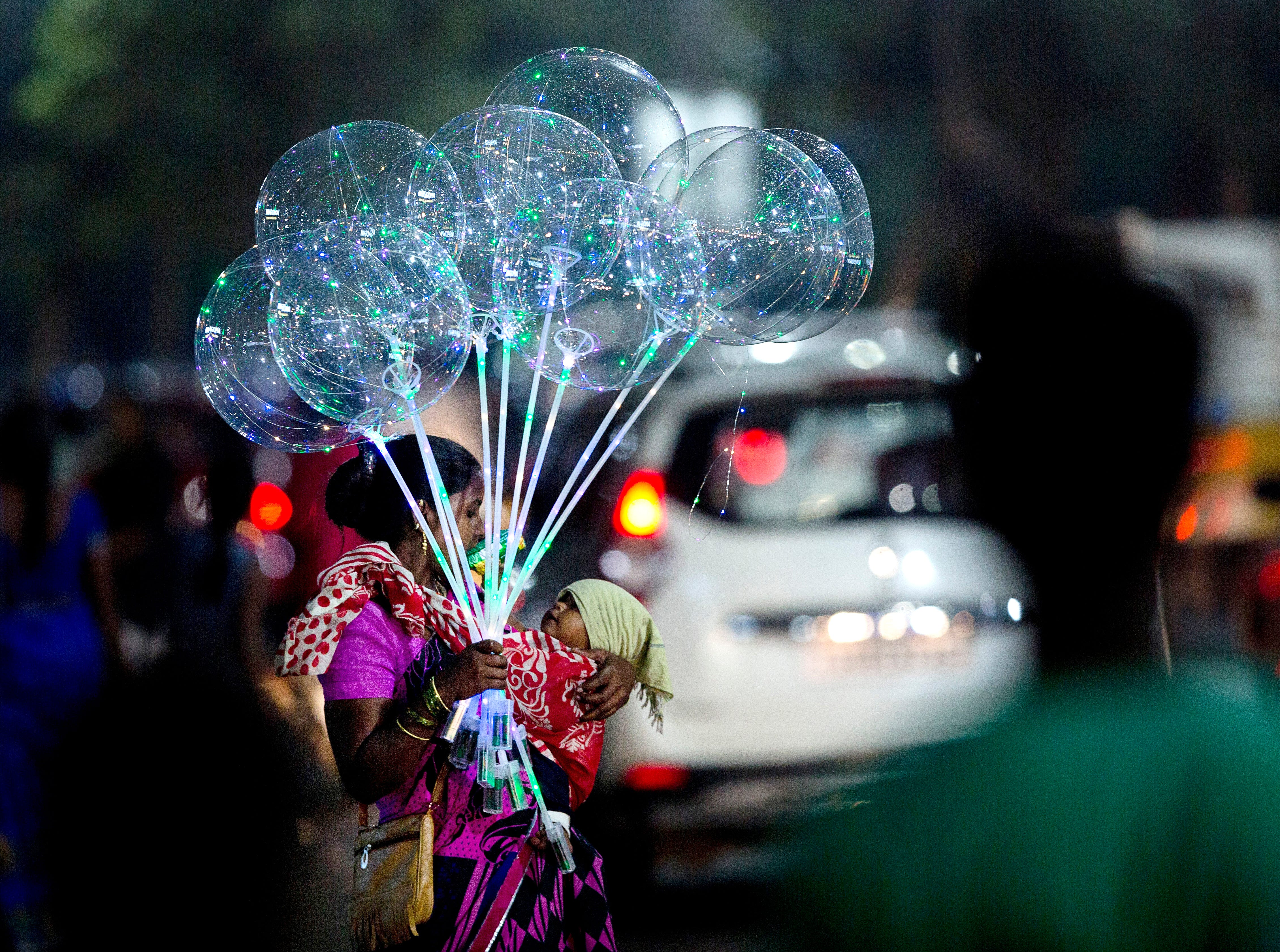 An Indian vendor carries an infant and stands on a street selling balloons in Hyderabad, Friday, Sept. 21, 2018. Some 800 million people in the country live in poverty, many of them migrating to big cities in search of a livelihood and often ending up on the streets.
