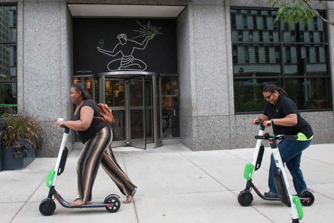 A pair of Lime scooter customers ride Lime scootersfor near Campus Martius Park in downtown Detroit on Tuesday, August 28, 2018.
