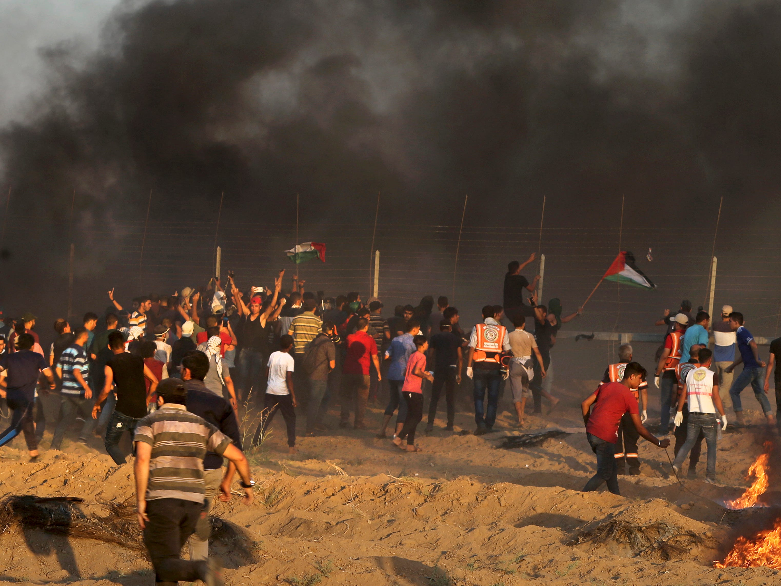Protesters break the fence of Gaza Strip border with Israel during a protest east of Gaza City, Friday, Sept. 21, 2018. Gaza's Health Ministry says a Palestinian was killed and dozens injured by Israeli fire at a border protest.