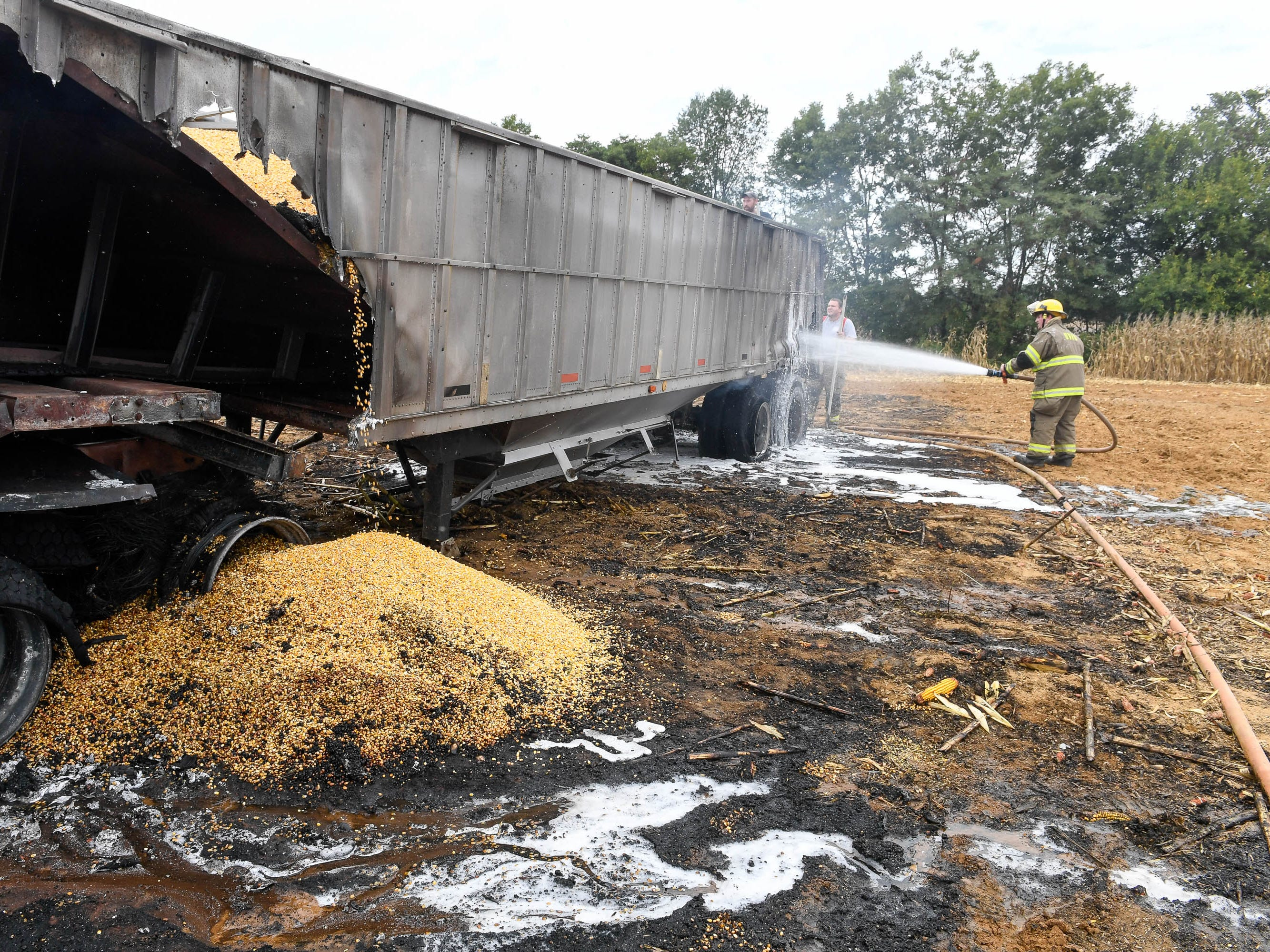 Volunteer firemen hose down hot spots after two semi-tractor trailers caught fire while harvesting corn on the Dale Dixon farm on Trigg-Turner Road in Henderson County Friday. September 21, 2018.