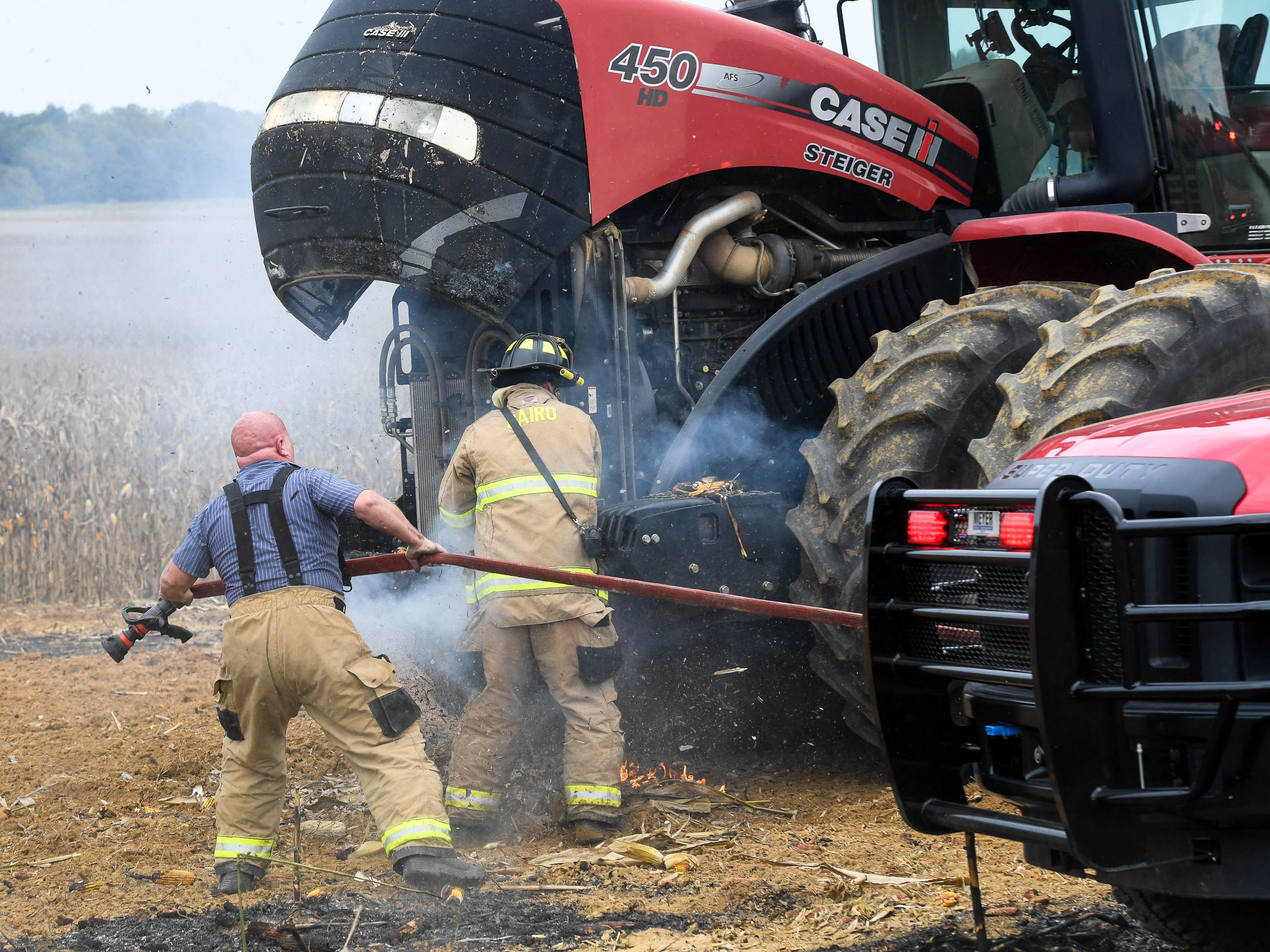 Volunteer firemen frantically remove burning corn debris from a tractor owned by Cory Duncan after he helped his neighbor, Dale Dixon, put out a fire in his corn field that burned two semi-tractor trailers while harvesting corn Friday. September 21, 2018.