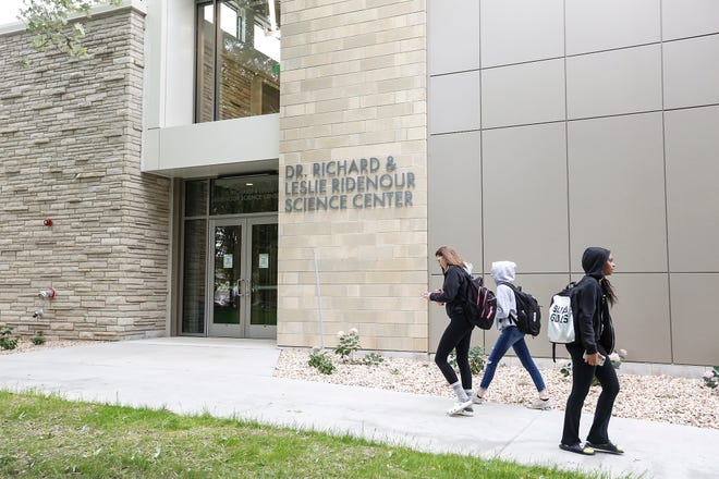 Students walk by the new Dr. Richard and Leslie Ridenour Science Center Friday on the Marian University campus.