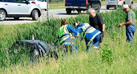 First responders attempt to assist a motorist Friday after a two-vehicle crash at U.S. 20 and Sandusky County Road 198.