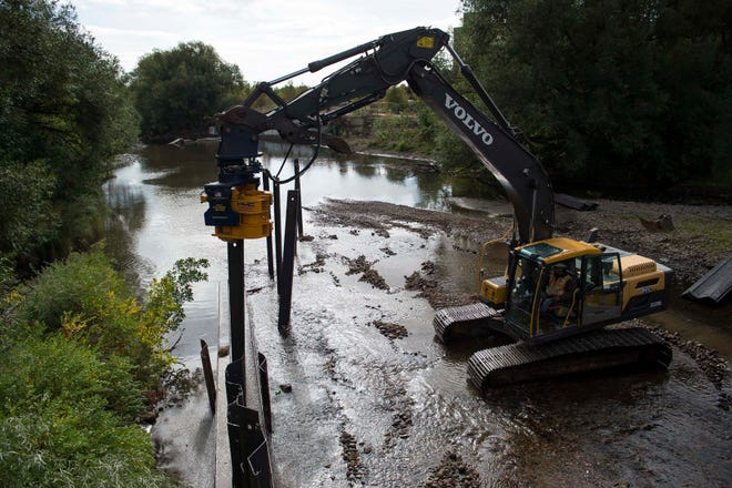 Construction workers drive a sheet pile wall into the riverbed to begin construction on the Poudre River Whitewater Park on Friday, Sept. 21, 2018, just West of the North College Avenue bridge over the Cache la Poudre River in Fort Collins, Colo.