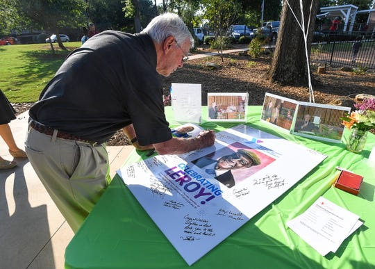 Fred Graham signs a poster for Leroy Richardson, the longest-serving employee of the Greenville YMCA, during a retirement party for Richardson at the Caine Halter Family YMCA in Greenville Thursday, September 20, 2018.