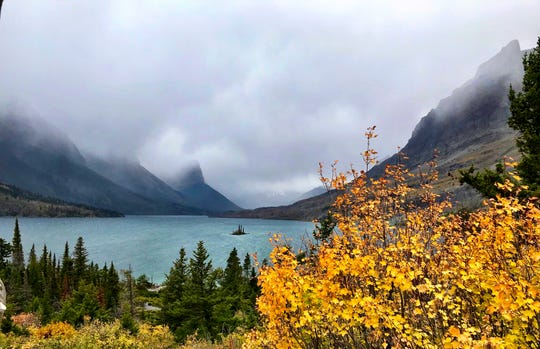 Wild Goose Island appears amid misty mountains along Going-to-the-Sun Road in Glacier National Park.