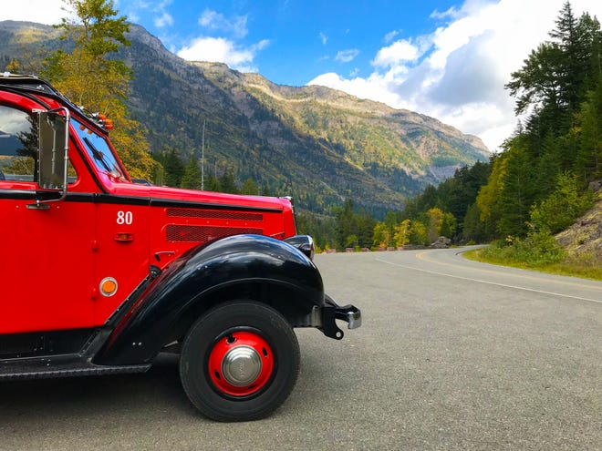 An iconic red bus makes one of its last drives over Going-to-the-Sun Road for the season in Glacier National Park.