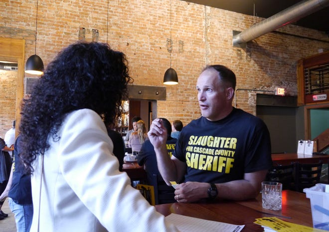 Jesse Slaughter, candidate for Cascade County Sheriff, speaks with a member of the public at a campaign event Wednesday, Sept. 12, 2018.