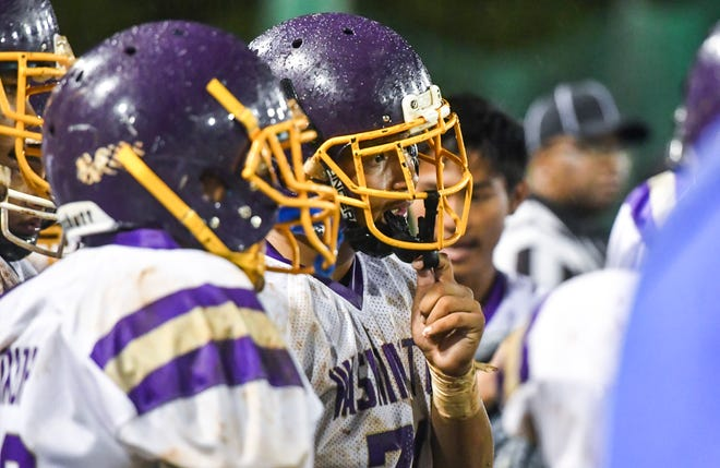 George Washington High School Geckos football players gather during a time out in this file photo from Sept. 21, 2018.