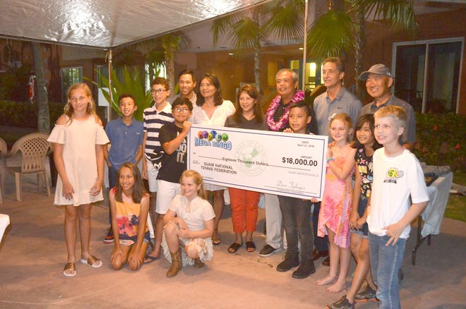 Community Corporation's David Tydingco, in center with orchid lei, presents a check for $18,000 to the Guam National Tennis Federation during the awards banquet of the 46th Annual Chamorro Open Tennis Tournament held earlier this year.