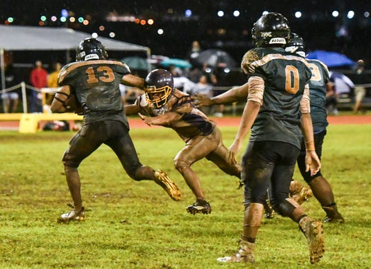 Light rainshowers made for slippery gameplay as the John F. Kennedy Islanders took on the challenge of the George Washington Geckos in an Interscholastic Football League matchup at Ramsey Field in Tamuning on Friday, Sept. 21, 2018.