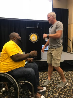 Dwight Owens, with Still Standing, introduces NFL Hall of Famer Brett Favre, as he prepares to speak to students with disabilities at the University of Southern Mississippi.