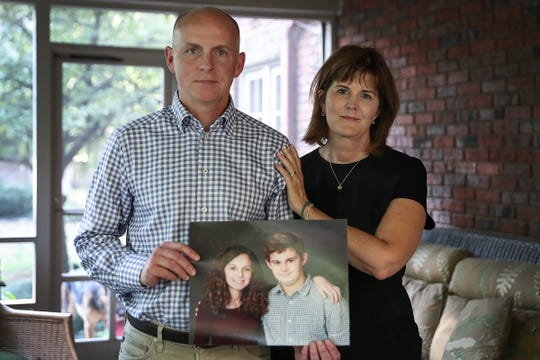"From left, JB and Suzann Lupton pose with a photo of their children Audrey and Andrew, taken at ages 14 and 18, at their home in Indianapolis, Thursday, Sept. 20, 2018. When Audrey, a 17-year-old University High School student, lost her battle with cancer in July 2017, she left bucket lists for her parents and brother. Suzann and JB said the lists are a mix of simple tasks and broad goals that encourage her parents to ""just keep living."" For example, Audrey wished for her mother to continue art lessons and for the family to travel."
