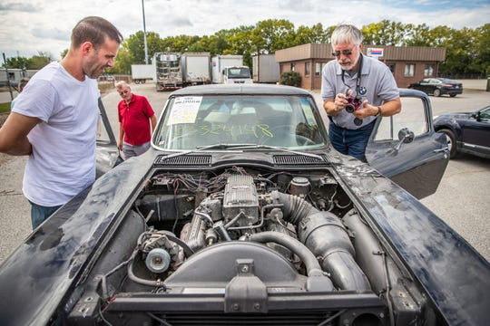 Gary Pasch, right, photographs the engine on his 1965 Chevy Corvette before the drive back to Rockford, Ill., on Friday, Sept. 21, 2018.