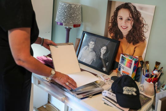 """Suzann Lupton flips through an art book her late daughter Audrey made, in Audrey's room at their home in Indianapolis, Thursday, Sept. 20, 2018. When the 17-year-old University High School student lost her battle with cancer in July 2017, she left bucket lists for her parents and brother. Suzann and JB said the lists are a mix of simple tasks and broad goals that encourage her parents to """"just keep living."""" For example, Audrey wished for her mother to continue art lessons and for the family to travel."""