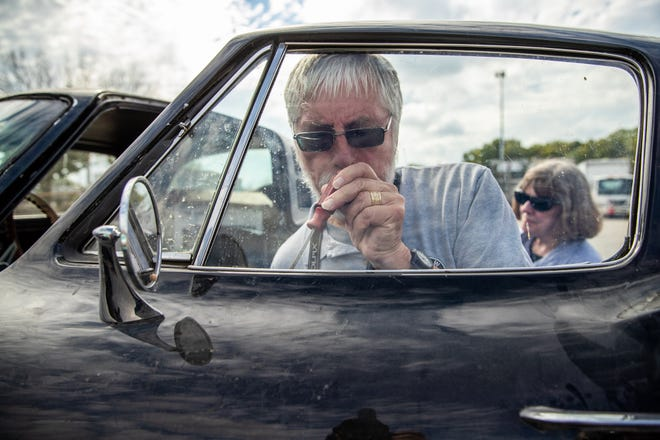 Gary Pasch attempts to fix the driver's side window on his 1965 Chevy Corvette that won't stay up before the drive back to Rockford, Ill., on Friday, Sept. 21, 2018.